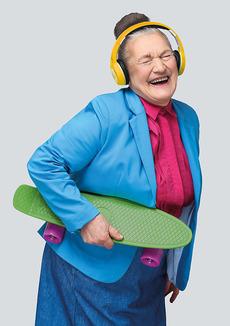lachende alte Frau mit Kopfhörern auf den Ohren und Skateboard in der Hand