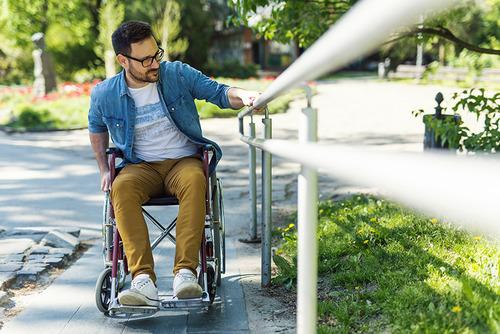 junger Mann in Rollstuhl fährt eine Rampe hoch und hält sich dabei an einem weißen Geländer fest