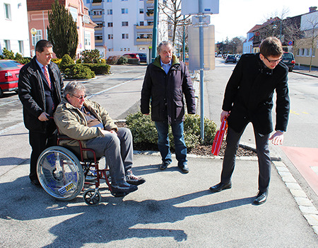 Drei Männer stehen, ein Mann sitzt im Rollstuhl, vor einem Zebrastreifen. Sie begutachten die Höhe der Randsteinkante, im Rahmen einer Gemeindebegehung.