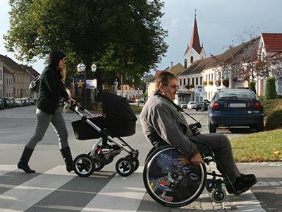 eine Frau mit Kinderwagen und ein Rollstuhlfahrer überqueren eine Straße auf einen Zebrastreifen