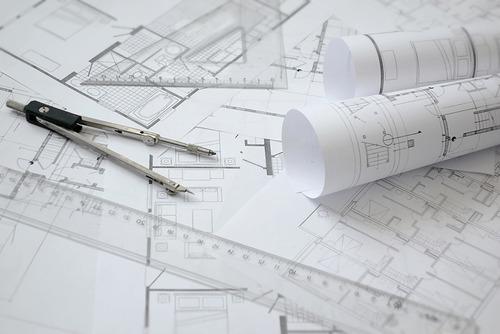 Architekturpläne, ein Lineal und ein Zirkel