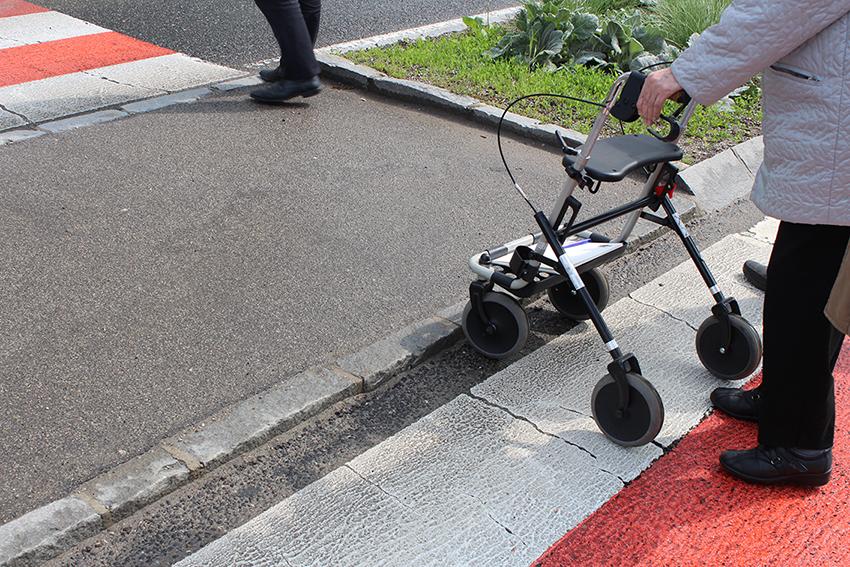 ältere Frau mit Rollator überquert einen Zebrastreifen