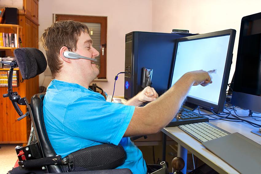 junger Mann im Rollstuhl mit Headset im Ohr, deutet auf einen Bildschirm der vor ihm steht