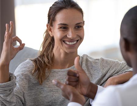 Lächelnde Frau gebärdet mit einem Mann.