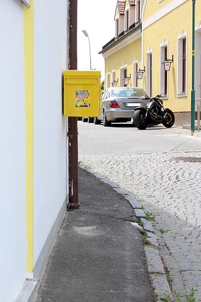Gehweg an der Ecke eines Hauses. Der Weg ist sehr schmal und am Hauseck hängt in Brusthöhe ein Briefkasten.