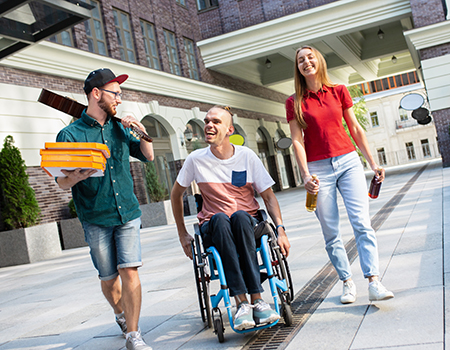 Drei junge Erwachsene gehen lachend über einen betonierten Platz. Ein junger Mann trägt Pizzakartons, in der Mitte ist ein junger Rollstuhlfahrer und rechts neben ihm geht eine junge Erwachsene mit Limonadenflaschen in der Hand.