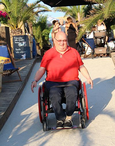 Richard J. Schäfer fährt im Rollstuhl einen Strandweg entlang.