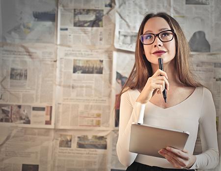 Junge Frau mit einem Tablet in der Hand, einen Stift hält sie nachdenklich an ihr Kinn. Im Hintergrund erkennt man eine Wand, die mit Zeitungen bekleidet ist.