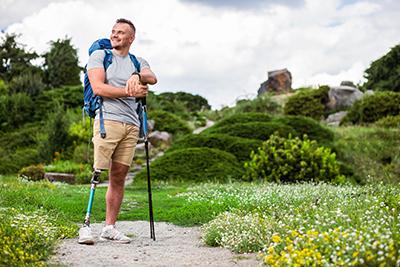 Junger Mann mit Beinproteste beim Wandern in einer grünen Landschaft