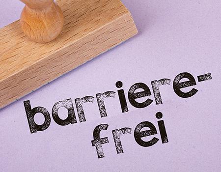 Ein Holzstempel, daneben sieht man in gestempelter Form den Schriftzug barrierefrei.