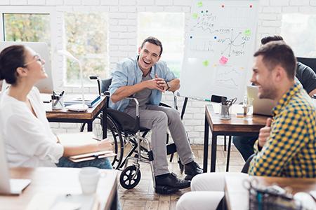 Eine Frau und zwei Männer, davon sitzt einer im Rollstuhl, diskutieren und lachen in einem modernen Büro.